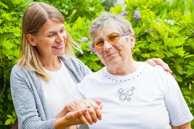 Picture of a happy senior lady wearing glasses with her caregiver in the garden