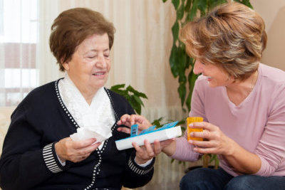caregiver suggesting medicine to a senior woman