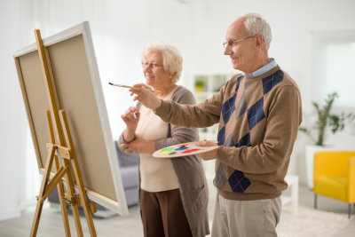 senior man and woman painting something at home